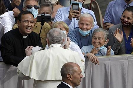 Papst Franziskus (M, 2.v.vorne) trifft zu seiner ersten Generalaudienz mit Gläubigen seit Ausbruch der Corona-Pandemie ein. Foto: Andrew Medichini/AP/dpa