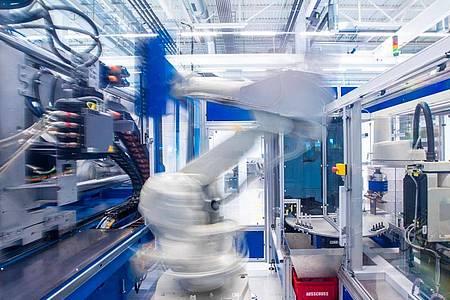 Ein Industrieroboter nimmt unter Reinraumbedingungen einen Halter für Insulinspritzen in einer Produktionshalle eines neu errichteteten Werks des Schweizer Medizintechnikunternehmens Ypsomed aus einer Maschine. Foto: Jens Büttner/dpa-Zentralbild/dpa