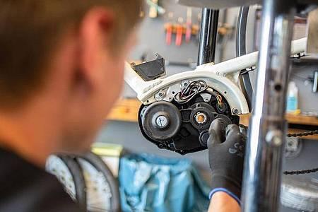 Fahrräder sind inzwischen oft Hightech-Maschinen: Zweiradmechatroniker wie Stefan Borschert müssen sich auch mit Motoren von E-Bikes auskennen. Foto: Nicolas Armer/dpa-tmn