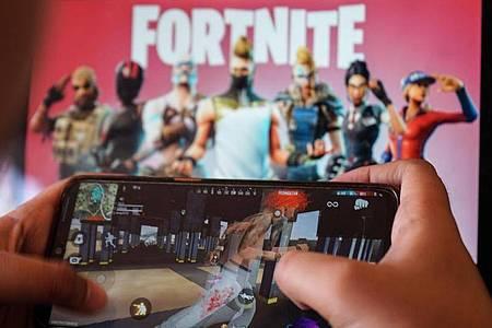 Ein Kind spielt ein Spiel auf einem Mobiltelefon mit einem Bild des Fortnite-Spiels auf dem Computerbildschirm im Hintergrund. (Archivbild). Foto: Herwin Bahar/ZUMA Wire/dpa