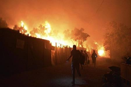 Menschen bringen sich vor denFlammen inSicherheit. Foto: Panagiotis Balaskas/AP/dpa