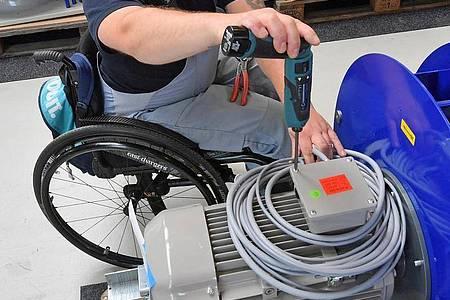 An einem Arbeitsplatz für Motorklemmen ist ein Mitarbeiter im Rollstuhl mit Montagearbeiten beschäftigt. Foto: Hendrik Schmidt/zb/dpa
