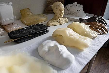 Auf dem Tisch im Arbeitszimmer von Janika Kreutzer liegen Abdrücke und Formen, die sie für die Verstorbenen verwendet. Foto: Fabian Sommer/dpa
