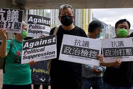 Der pro-demokratische Aktivist Lee Cheuk-yan (m.) während eines Protests vor einem Gericht. Foto: Vincent Yu/AP/dpa