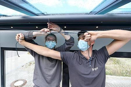 Sonnen- und Virenschutz: Laura Walig (l) und ihr Ausbilder Manuel Berger fixieren eine Unterglasmarkise. Als Hygienemaßnahme in Zeiten von Corona tragen sie eine Maske. Foto: Tobias Hase/dpa-tmn