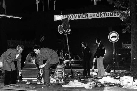 Nach dem Anchlag am 26. September 1980 wird ein Sarg vom verwüsteten Tatort auf dem Oktoberfest getragen. Foto: Frank Leonhardt/dpa