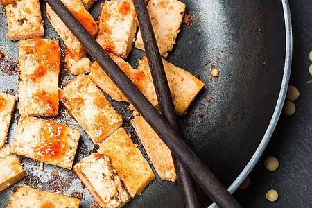 In Sojasauce marinierter und gebratener Tofu wird noch knuspriger, wenn man zuvor Flüssigkeit herauspresst. Foto: Franziska Gabbert/dpa-tmn