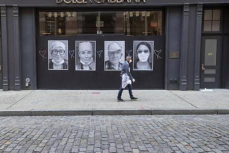 Ein Mann mit Mundschutz geht an einer geschlossenen Boutique in New York vorbei. Foto: Mary Altaffer/AP/dpa