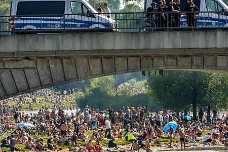 Dicht an dicht liegen die Menschen bei sommerlichen Temperaturen an der Isar. Foto: Peter Kneffel/dpa