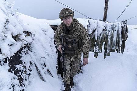 Ein ukrainischer Soldat gehen entlang eines schneebedeckten Schützengrabens, um die Position seiner Truppen an der Frontlinie zu bewachen. (Archivbild). Foto: Evgeniy Maloletka/AP/dpa