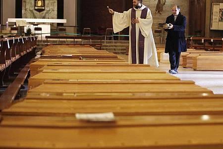 Ein Priester segnet Särge in Seriate, einer Gemeinde in der italienischen Provinz Bergamo. Foto: Antonio Calanni/AP/dpa