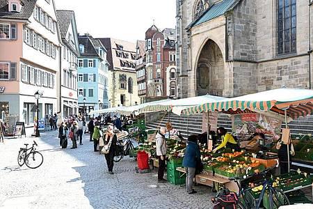 Passanten gehen in der Fußgängerzone an Marktständen vorbei. Foto: Bernd Weißbrod/dpa