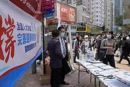Noch Mitte März sammelten Pro-China-Mitarbeiter in Hongkong die Unterschriften von Anwohnern zur Unterstützung eines Vorschlags zur Änderung der Wahlregeln. Foto: Kin Cheung/AP/dpa