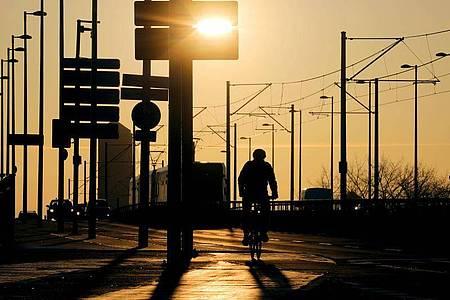 Ein Radfahrer fährt über die Deutzer Brücke in Köln. Die Zahl der Corona-Neuinfektionen steigt. Foto: Oliver Berg/dpa