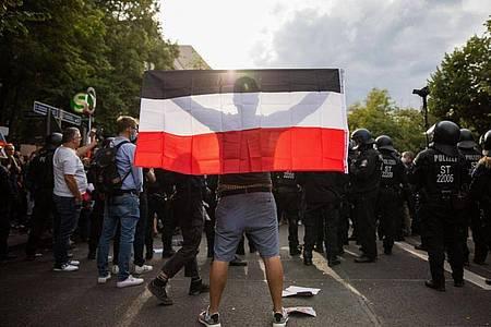 Ein Mann hält eine Reichsflagge bei einem Protest gegen die Corona-Maßnahmen. Foto: Christoph Soeder/dpa/Christoph Soeder