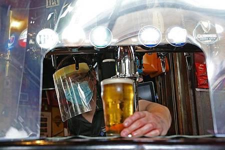 Ein Barkeeper im Pub zapft ein Glas Bier mit Mundschutz und Visier vor der Wiedereröffnung. Foto: Yui Mok/PA Wire/dpa