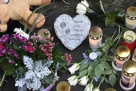 KErzen und Blumen: Vor dem Haus fand eine kleine Trauerfeier statt. Foto: Roberto Pfeil/dpa