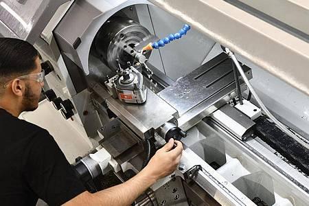 Der angehende Industriemechaniker Mohammed Elosrouti bearbeitet an der Drehmaschine ein Werkstück. Foto: Kirsten Neumann/dpa-tmn