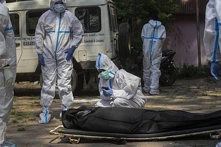 Die Verlobte eines an den Folgen einer Corona-Infektion Verstorbenen bricht während der Einäscherung zusammen. Foto: Anupam Nath/AP/dpa