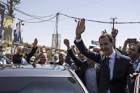 Baschar al-Assad (r), Präsident von Syrien, kommt an einem Wahllokal während der Präsidentschaftswahlen an. Foto: Hassan Ammar/AP/dpa
