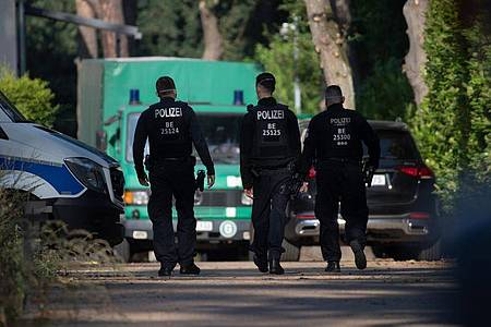 Polizeibeamte sind im Rahmen einer Durchsuchung auf einem Grundstück in Brandenburg unterwegs. Foto: Paul Zinken/dpa-Zentralbild/dpa