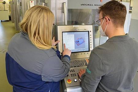 Technische Unterstützung: Pascal Scheu und seine Ausbilderin Vanessa Gfell sehen sich gemeinsam die Arbeitsschritte an der Fräsmaschine an. Foto: B. Braun Melsungen AG/dpa-tmn