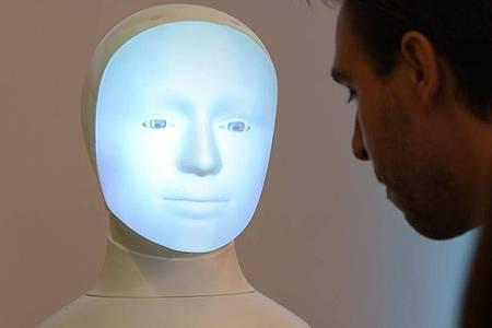 """Patrick Schanowski, wissenschaftlicher Mitarbeiter, kommuniziert während einer Pressekonferenz an der TU Darmstadt mit Roboter """"Alfie"""", einer Moral Choice Machine. Foto: Arne Dedert/dpa"""