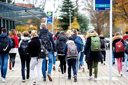 Schülerinnen und Schüler gehen mit ihren Schulrucksäcken von einer Bushaltestelle zu ihrer Schule in Niedersachsen. Foto: Hauke-Christian Dittrich/dpa