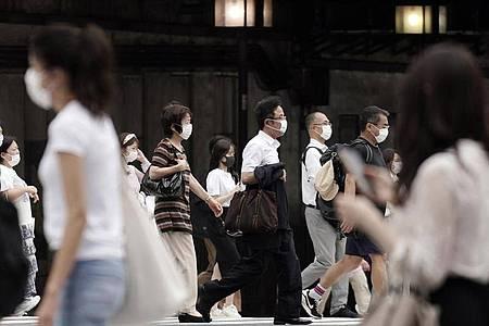 Passanten mit Mund-Nasen-Schutz in Tokio. Foto: Eugene Hoshiko/AP/dpa