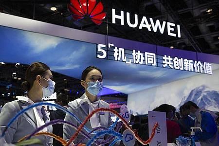 Mitarbeiter stehen an einem Stand des chinesischen Technologieunternehmens Huawei auf der PT Expo in Peking. Foto: Mark Schiefelbein/AP/dpa