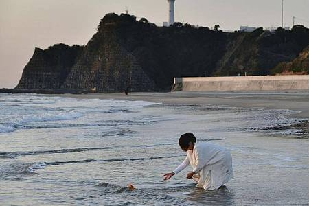 Eine Frau legt Blumen an einem Strand in der vom Tsunami verwüsteten nordostjapanischen Stadt Iwaki in der Präfektur Fukushima ab. Japan beging gerade erst den 10. Jahrestag der Erdbeben-, Tsunami- und Nuklearkatastrophe. Foto: ---/kyodo/dpa