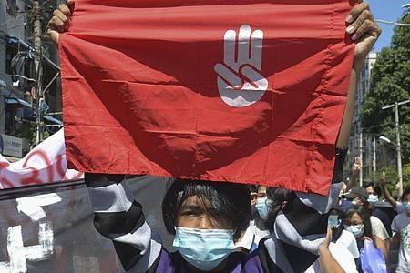 Ein Protestteilnehmer hält während einer Demonstration in Yangon eine Flagge hoch, auf der das Drei-Finger-Zeichen des Widerstandes zu sehen ist. Foto: Uncredited/AP/dpa