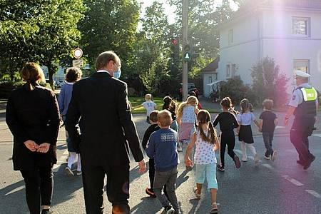 Landrat Dr. Olaf Gericke zusammen mit Polizistinnen und Polizisten, Eltern, Lehrern und den Kindern der Klasse 1 der Barbaragrundschule in Ahlen beim Überqueren der Straße.