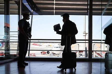 Beamte der Bundespolizei kontrollieren im Terminal 1 des Flughafen Hamburg Passagiere eines ankommenden Flugzeugs. Foto: Christian Charisius/dpa