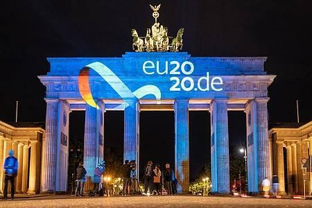 Das Logo der deutschen Ratspräsidentschaft wird auf das Brandenburger Tor inBerlin projiziert. Foto: Christophe Gateau/dpa