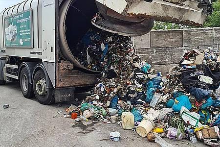 Ein Müllwagen hat Hausmüll abgekippt. Ein täuschend echt aussehender Kopf in einem Müllberg hat in Gelsenkirchen für Erschrecken gesorgt. Foto: Polizei Gelsenkirchen/dpa