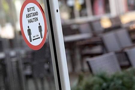 Ein Aufkleber mit der Aufschrift «Bitte Abstand halten» klebt an einer Scheibe. Strenge Kontaktbeschränkungen gehören einer aktuellen Studie zufolge zu den wirksamsten Corona-Maßnahmen. Foto: Federico Gambarini/dpa