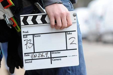 Ein Mitarbeiter eines Filmteams hält eine Filmklappe. Foto: Tobias Hase/dpa