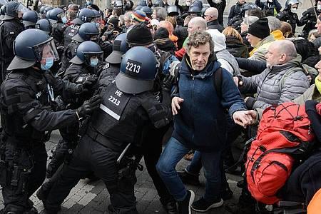 Einsatzkräfte der Polizei halten bei einer Kundgebung Teilnehmer zurück. Foto: Swen Pförtner/dpa