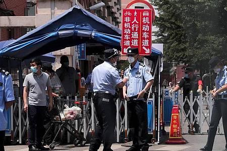 Polizeibeamte und Sicherheitsbeamte stehen vor Wohngebäuden Wache, die nach einem positiven Fall auf einem nahe gelegenen Markt abgeriegelt wurden. Foto: Andy Wong/AP/dpa