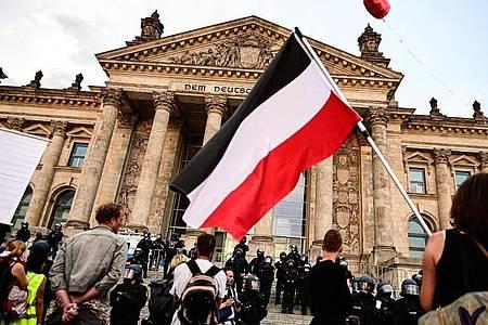 Teilnehmer einer Kundgebung gegen die Corona-Maßnahmen stehen Ende August vor dem Reichstag, ein Teilnehmer hält eine Reichsflagge. Foto: Fabian Sommer/dpa