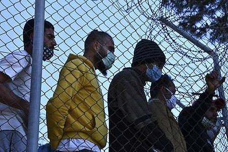 Migranten in einem Flüchtlingscamp am Hafen von Vathy auf der Insel Samos beobachten den Besuch der EU-Innenkommissarin Johansson. Foto: Michael Svarnias/AP/dpa