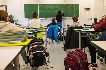 Schülerinnen und Schüler einer fünften Klasse sitzen während dem Unterricht in ihrem Klassenzimmer. Foto: Philipp von Ditfurth/dpa