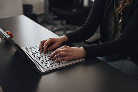 Frau tippt auf Laptop