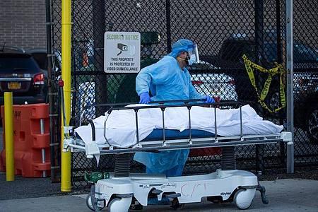 Ein medizinischer Mitarbeiter überführt den Leichnam eines Coronavirus-Opfers in New York. Foto: Michael Nagle/XinHua/dpa