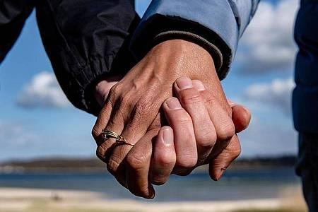 Eine Frau und ein Mann halten sich bei einem Strandspaziergang an den Händen. Foto: Axel Heimken/dpa