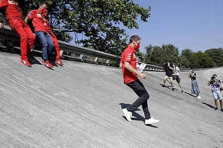 Ferrari-Pilot Sebastian Vettel läuft die Steilkurve der alten Rennstrecke von Monza ab. Foto: Luca Bruno/AP/dpa