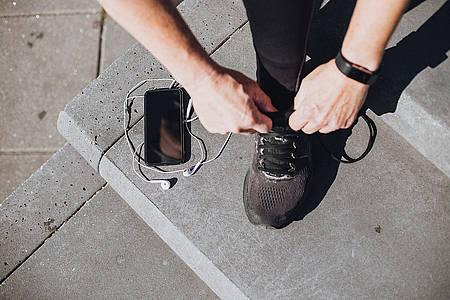 Mann bindet sich seinen Laufschuh