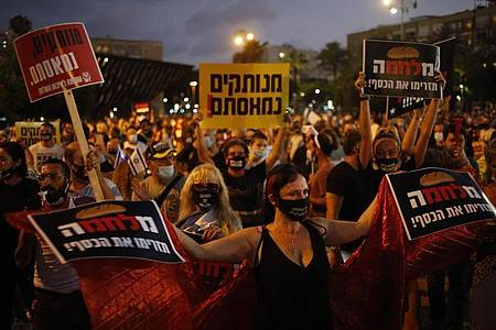 Tausende Israelis versammelten sich auf dem Rabin-Platz in Tel Aviv um gegen den Premierminister Netanjahu und die wirtschaftliche Notlage des Landes aufgrund der Corona-Pandemie zu demonstrieren. Foto: Ariel Schalit/AP/dpa