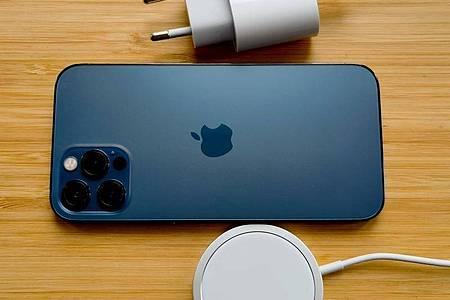 Ein Ladegerät liefert Apple bei iPhone 12 nicht mehr mit, nur noch ein Ladekabel. Für ein USB-C-Netzteil (oben im Bild) verlangt Apple 24 Euro und für das Drahtlosladesystem Magsafe (unten) 44 Euro. Foto: Christoph Dernbach/dpa-tmn